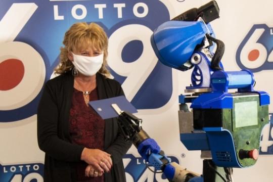 Un robot lui remet son chèque du Loto 6-49 Canadien
